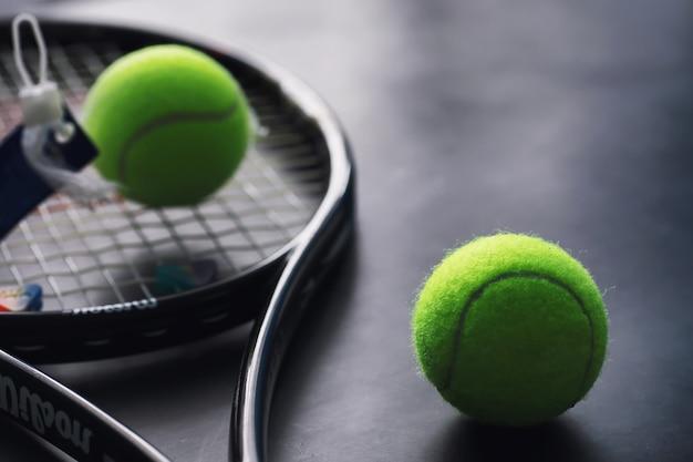 Sport und gesunder lebensstil. tennis. gelber ball für tennis und schläger auf dem tisch. sporthintergrund mit tenniskonzept.