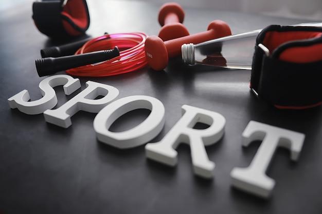 Sport und gesunder lebensstil. zubehör für den sport. yogamatte hantel und springseil. sporthintergrund mit heimübungskonzept.