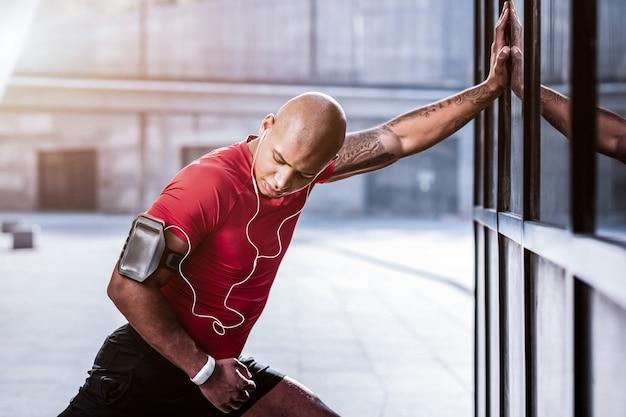 Sport und leben. hübscher athletischer mann, der seine hand während einer sportübung betrachtet
