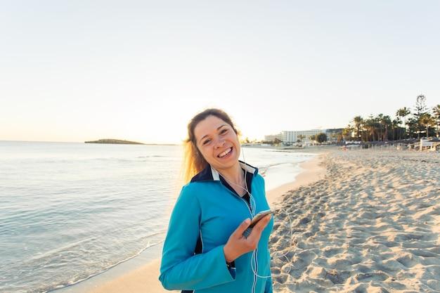 Sport- und lifestyle-konzept - frau nach dem laufen mit kopfhörern im freien.