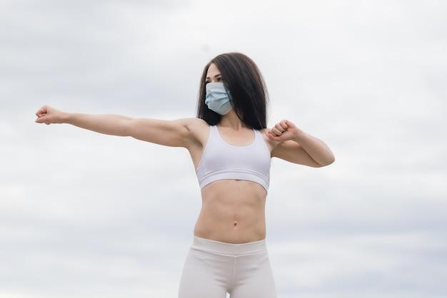 Sport während der quarantäne, coronavirus, covid-19. junge sportliche frau mit medizinischer schutzmaske