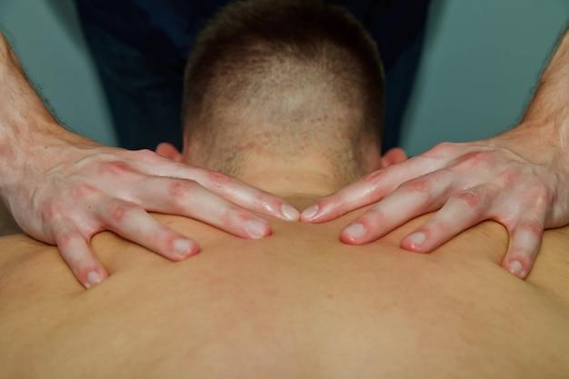 Sport wellness-massage im medizinischen raum des fitness-studios. masseur macht massageübungen. therapeutische regenerierende massage des sportkörpers. konzepte der rehabilitation von sportverletzungen. platz kopieren