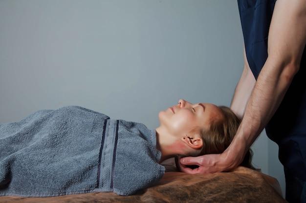 Sport wellness-massage im medizinischen raum des fitness-studios. masseur macht massageübungen. therapeutische regenerierende massage des sportkörpers