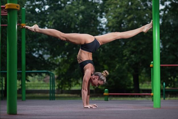 Sportakrobatikmädchen steht auf ihren händen und macht ein akrobatisches element