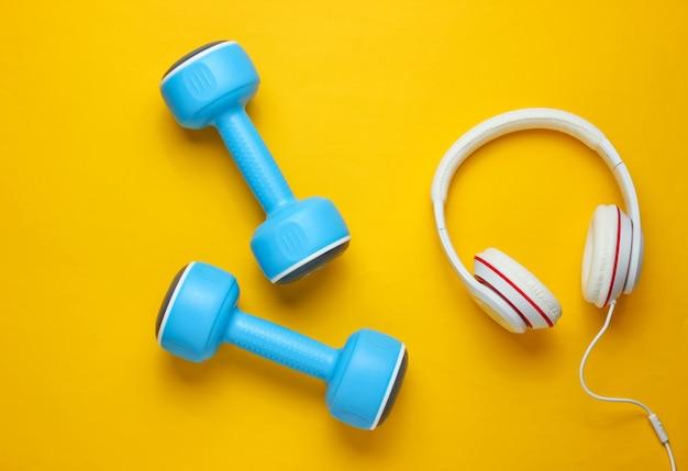 Sportausrüstung auf gelbem hintergrund. sportlicher lebensstil. kurzhanteln, kopfhörer. fitness-konzept.