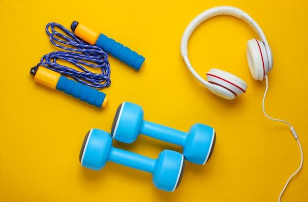 Sportausrüstung auf gelbem hintergrund. sportlicher lebensstil. kurzhanteln, kopfhörer, springseil. fitness-konzept.