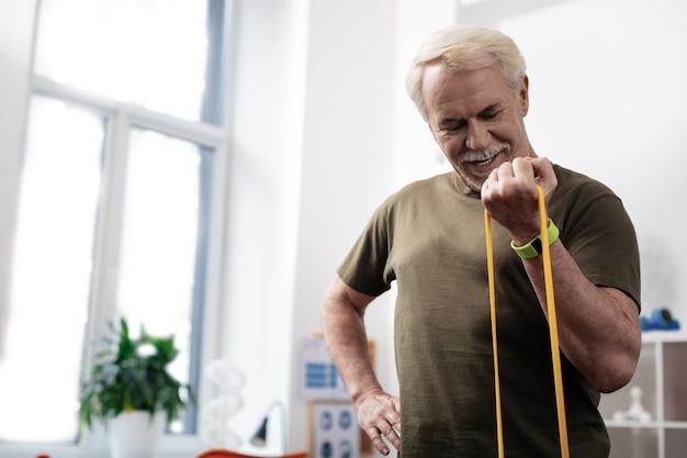 Sportausrüstung. fröhlicher starker mann, der beim training seinen arm mit einem gummiband streckt