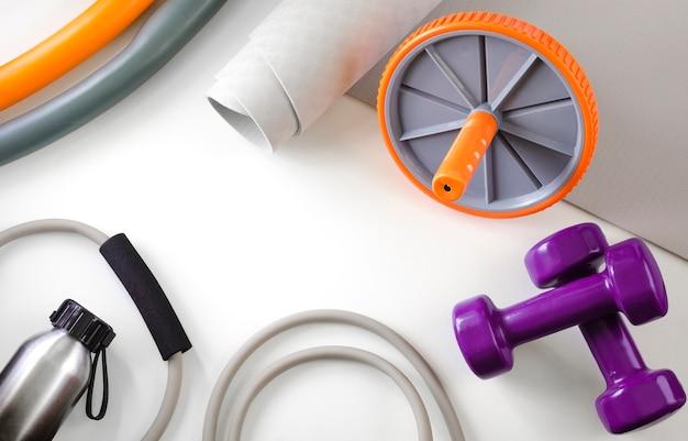 Sportausrüstung: hanteln, expander, yogamatte, walze für die presse, wasserflasche, reifen.