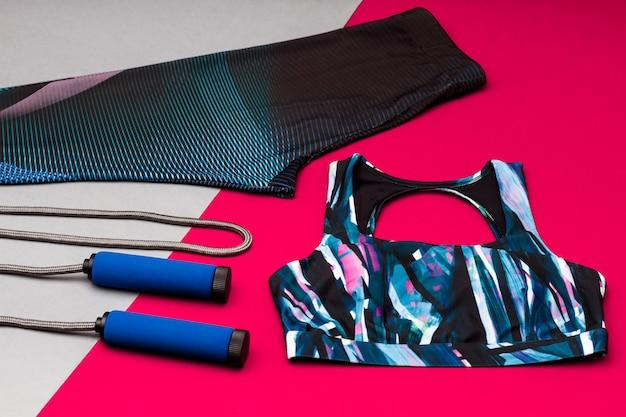 Sportausrüstung isoliert auf grauer und rosa oberfläche