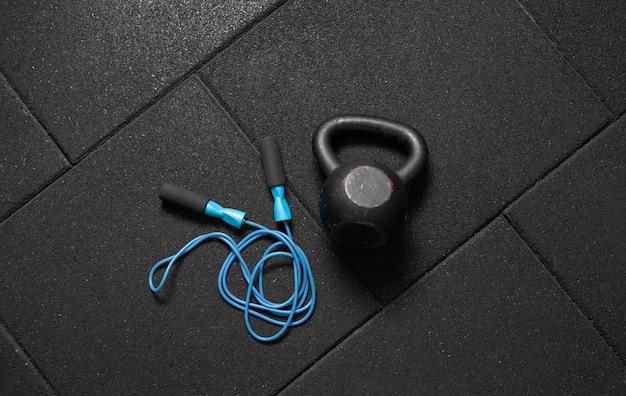 Sportausrüstung. kettlebell und springseil auf einem dunklen schwarzen boden. bodybuilding und fitness, funktionelles training