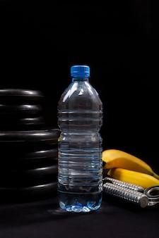 Sportausrüstung mit wasserflasche auf einem schwarzen