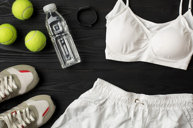 Sportausrüstung und abnutzung auf draufsicht des dunklen hölzernen hintergrundes