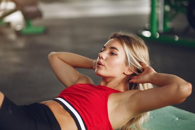 Sportblonde frau in einem sportbekleidungstraining in einem fitnessstudio
