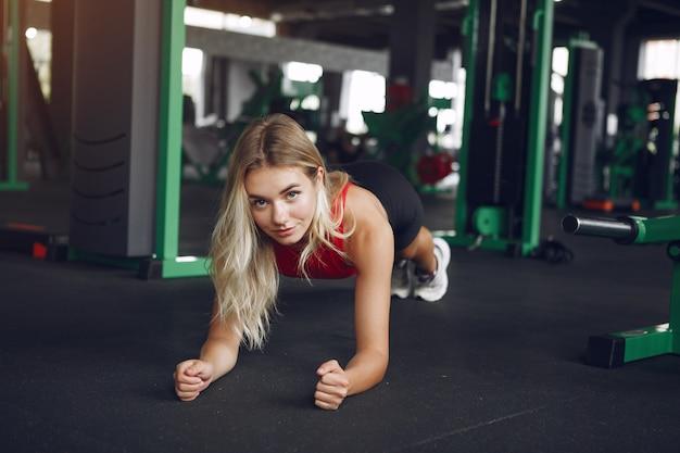 Sportblondine in einer sportbekleidung ruhen sich in einem fitnessstudio aus