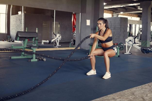 Sportbrünette frau in einem sportbekleidungstraining in einem fitnessstudio