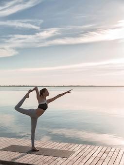 Sportdame, die am strand steht, macht yogaübungen.
