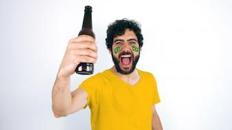 Sportfan mit Brasilien-Flagge auf seinem Gesicht, das ein Bier hält, das für den Triumph seines t schreit