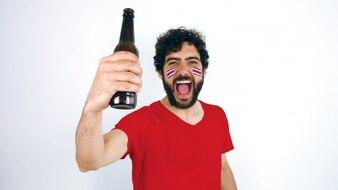 Sportfan mit Costa Rica-Flagge auf seinem Gesicht, das ein Bier hält, das für den Triumph von seinem schreit
