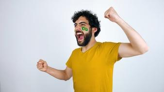 Sportfan mit der Brasilien-Flagge ist auf seinem Gesicht, das für den Triumph seines Teams schreit.