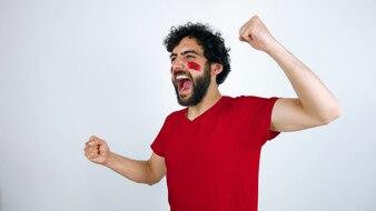 Sportfan mit der Marokko-Flagge auf seinem Gesicht, das den Triumph seines Teams feiert.