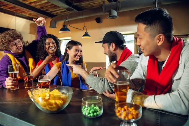 Sportfans jubeln an der bar, im pub und trinken bier während der meisterschaft, der wettbewerb geht. multiethnische gruppe von freunden aufgeregt, die übersetzung zu sehen. menschliche emotionen, ausdruck, unterstützendes konzept. Kostenlose Fotos