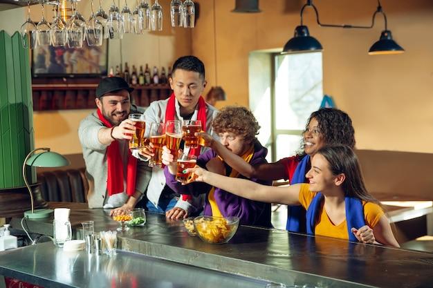 Sportfans jubeln an der bar, im pub und trinken bier während der meisterschaft, der wettbewerb geht. multiethnische gruppe von freunden aufgeregt, die übersetzung zu sehen. menschliche emotionen, ausdruck, unterstützendes konzept.