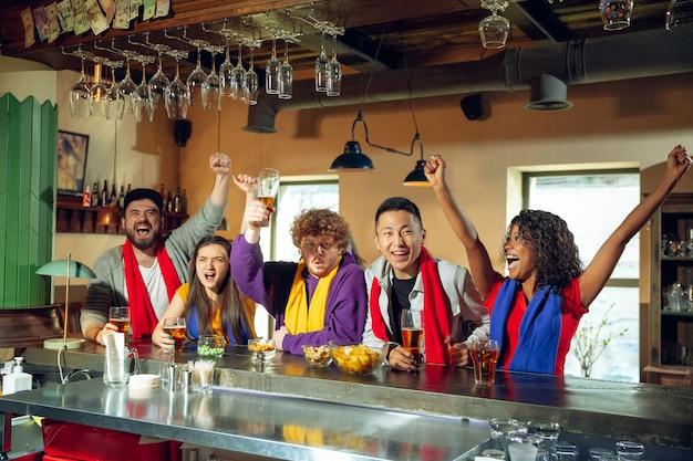 Sportfans jubeln an der bar, im pub und trinken bier während der meisterschaft, der wettbewerb läuft. multiethnische freundesgruppe.
