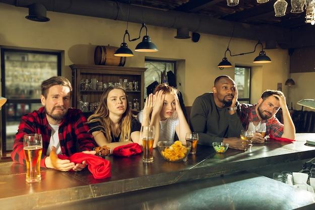 Sportfans jubeln an der bar, im pub und trinken bier während der meisterschaft, der wettbewerb läuft. multiethnische gruppe von freunden aufgeregt, die übersetzung zu sehen. menschliche emotionen, ausdruck, unterstützendes konzept.