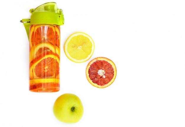 Sportflasche mit tropischen früchten auf einem weißen hintergrund