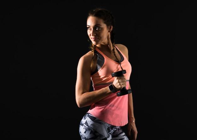 Sportfrau auf dem dunklen hintergrund, der gewichtheben macht
