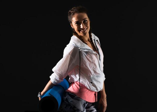 Sportfrau auf dunklem hintergrund mit matte
