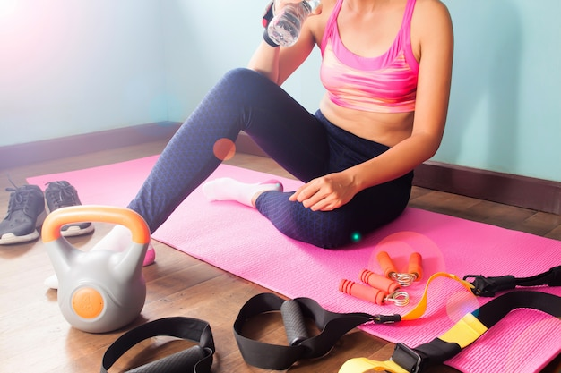Sportfrau, die auf rosa farbyogamatte sitzt