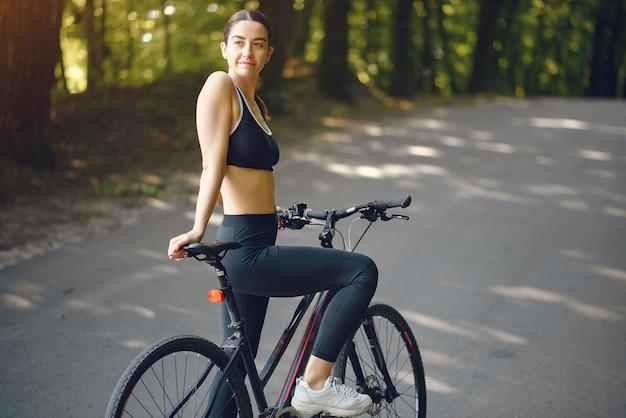 Sportfrau, die fahrräder im sommerwald reitet
