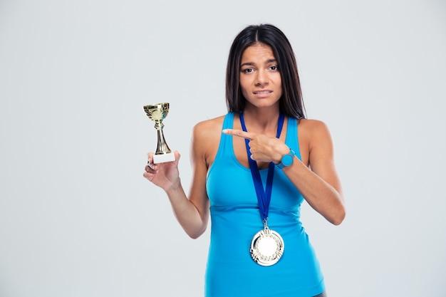 Sportfrau, die finger auf den siegerpokal zeigt