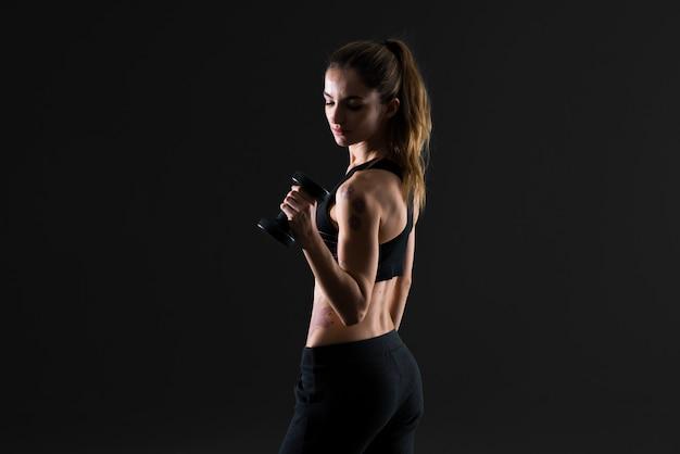 Sportfrau, die gewichtheben auf dunklem hintergrund macht