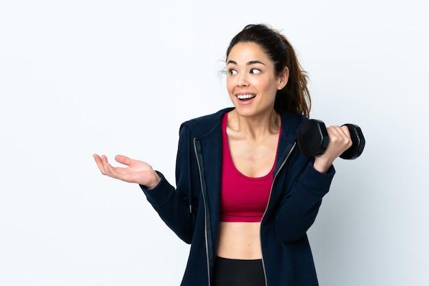 Sportfrau, die gewichtheben über isoliertem weiß mit überraschendem gesichtsausdruck macht
