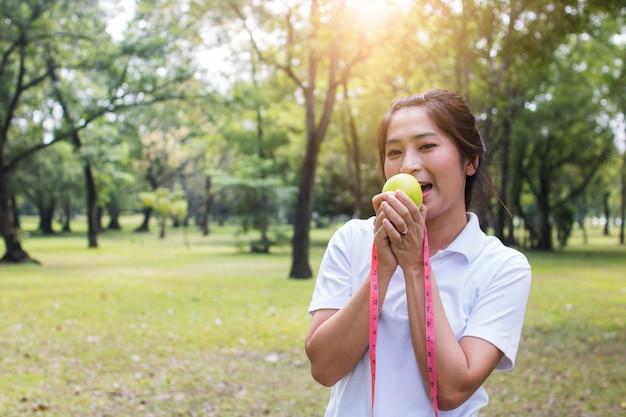 Sportfrau, die grünen apfel und das messen hält