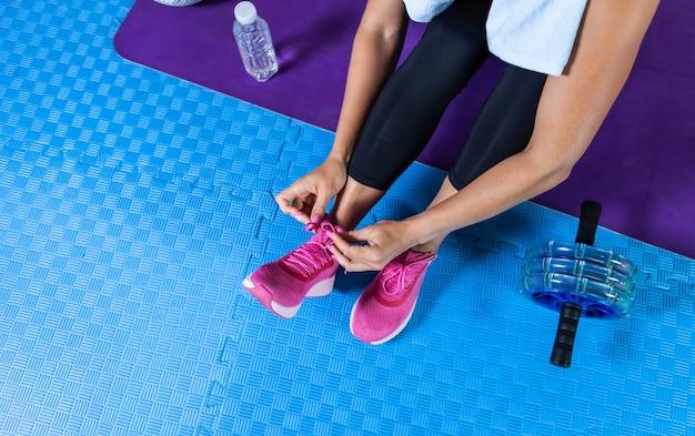 Sportfrau, die im fitnesskurs schnürsenkel an turnschuhen bindet