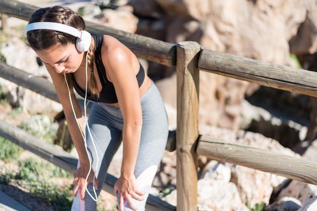 Sportfrau, die nach dem joggen in einem park im freien ruht
