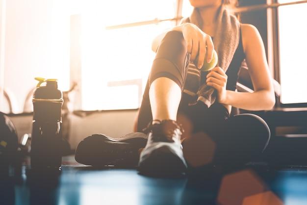 Sportfrau, die nach training oder übung in der eignungsturnhalle mit proteinshake sitzt und stillsteht