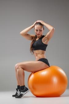 Sportfrau, die übungen auf einem fitball macht