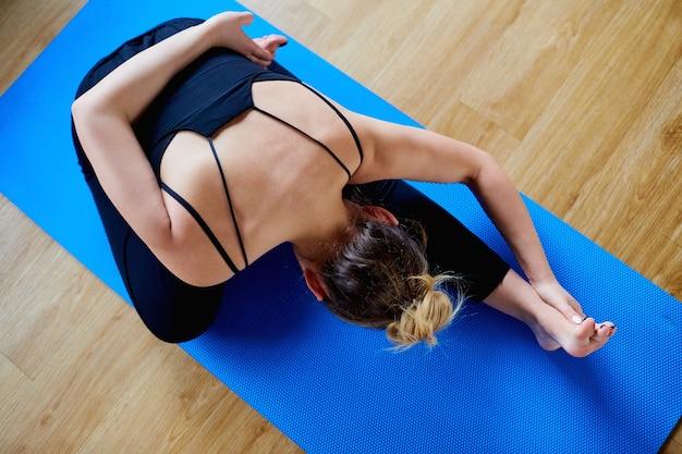 Sportfrau, die yoga in der turnhalle macht