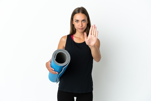 Sportfrau, die zu yoga-kursen geht, während sie eine matte über isoliertem weißem hintergrund hält und eine stopp-geste macht