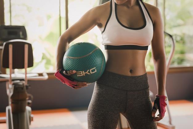 Sportfrau fit medizinballtraining im fitnessraum. sport entspannung und gesundes leben in innenräumen oder sportanlagen, um den muskel zu stärken.