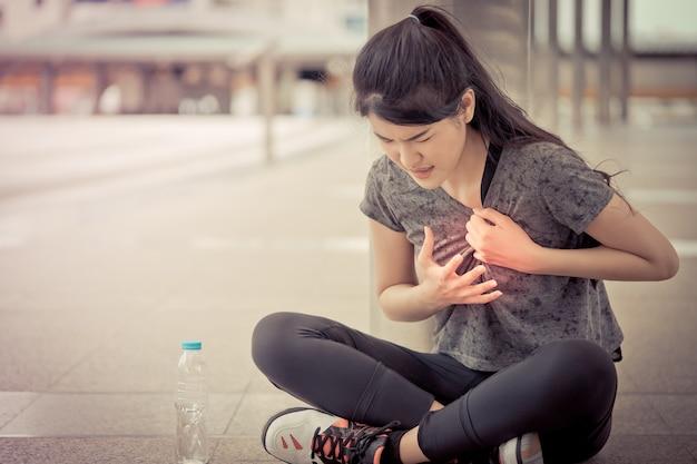 Sportfrau hat eine verletzung auf ihrem herzkasten-krankheitsangriff