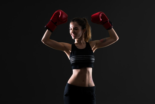 Sportfrau mit boxhandschuhen auf dunklem hintergrund