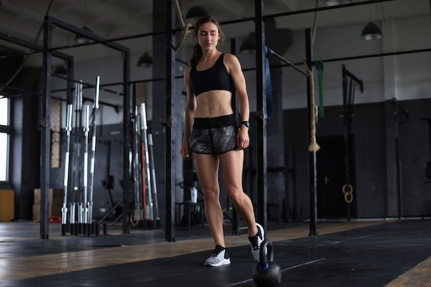 Sportfrau mit kettlebell in der turnhalle.