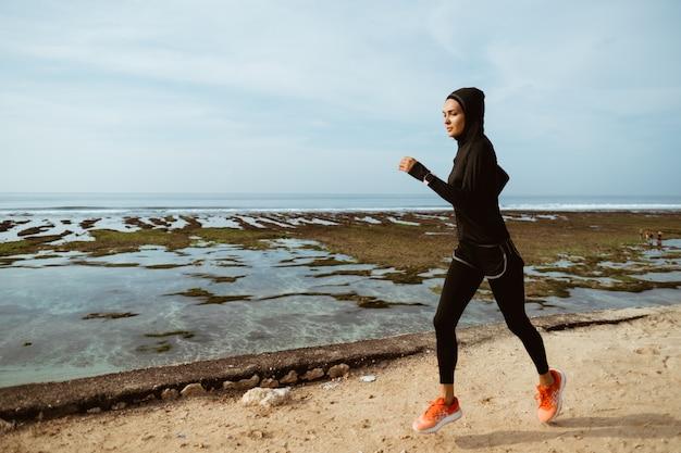 Sportfrau mit kopftuch läuft