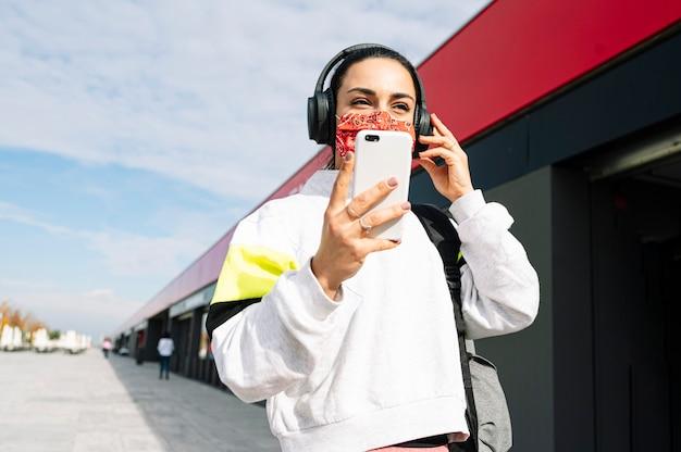 Sportfrau mit maske, die musik mit kopfhörern und smartphone hört