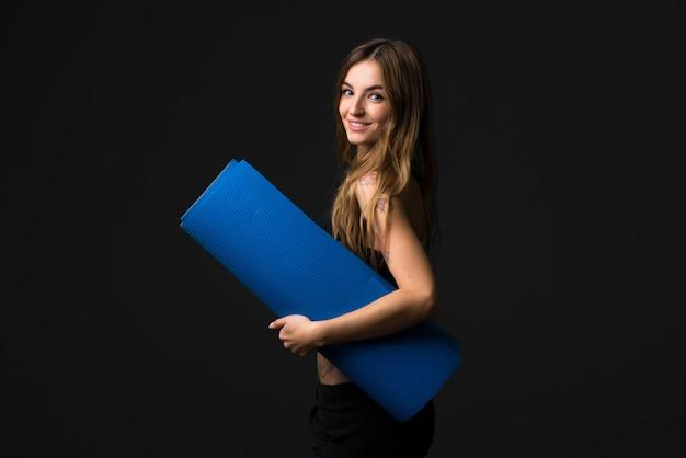 Sportfrau mit matte auf dunklem hintergrund